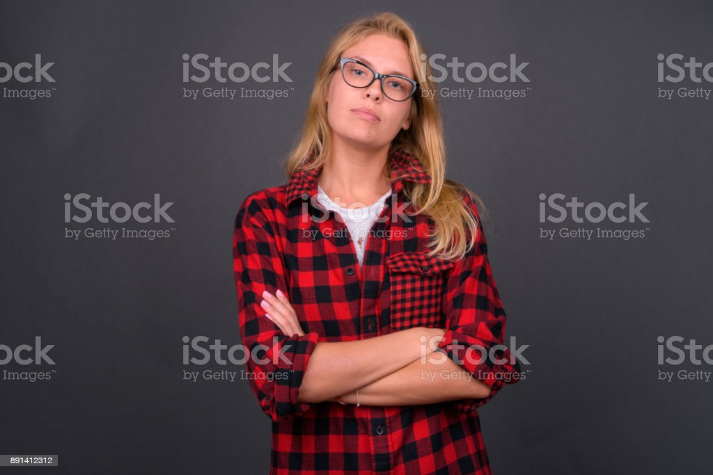 Portrait of young blonde woman with blue eyes against gray background stock photo