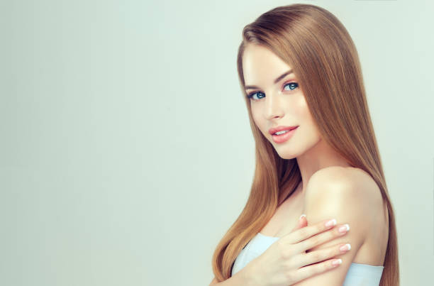 Portrait of young, blue eyed woman with long straight, shiny hair and delicate makeup on pretty face. stock photo