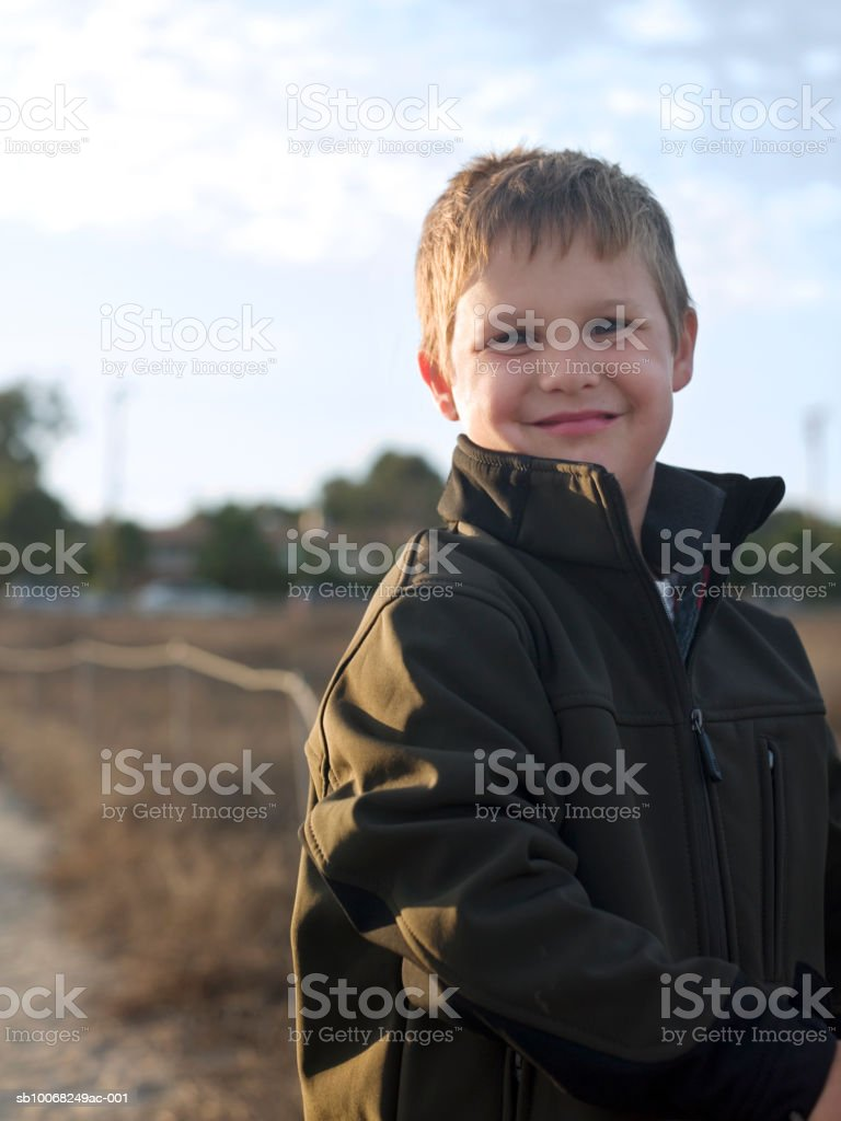 Portrait of young boy (6-7) in jacket at beach royalty-free stock photo