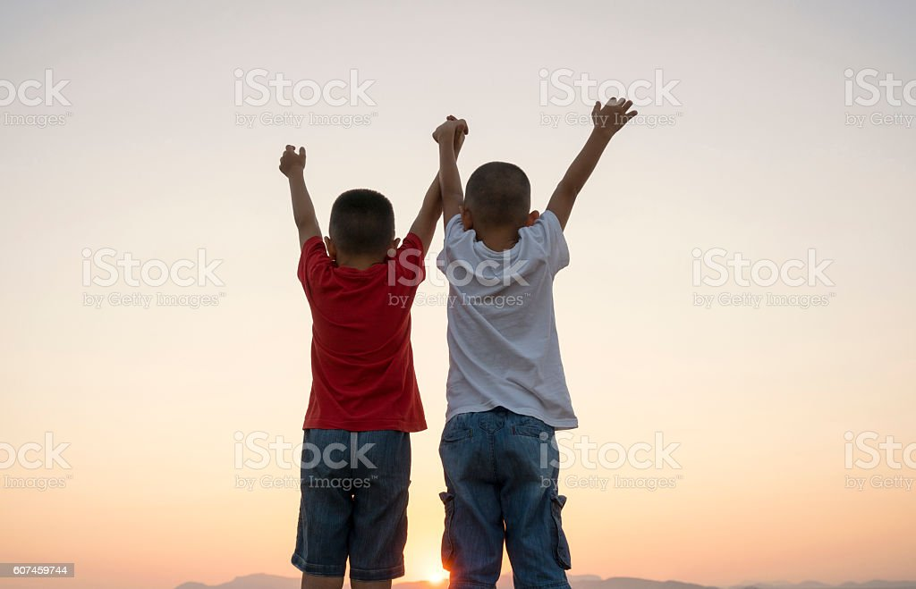 Portrait of young boys arms outstretched in nature stock photo