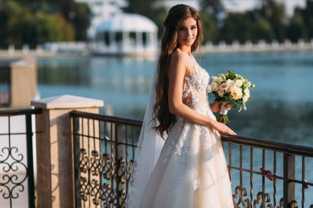 porträt der jungen braut mit langen haaren halten ihre hochzeit bouquet umfasst weiße rosen und andere blumen. schöne weiße hochzeit kleid. hübsches mädchen auf see hintergrund - hochzeitsfrisur boho stock-fotos und bilder