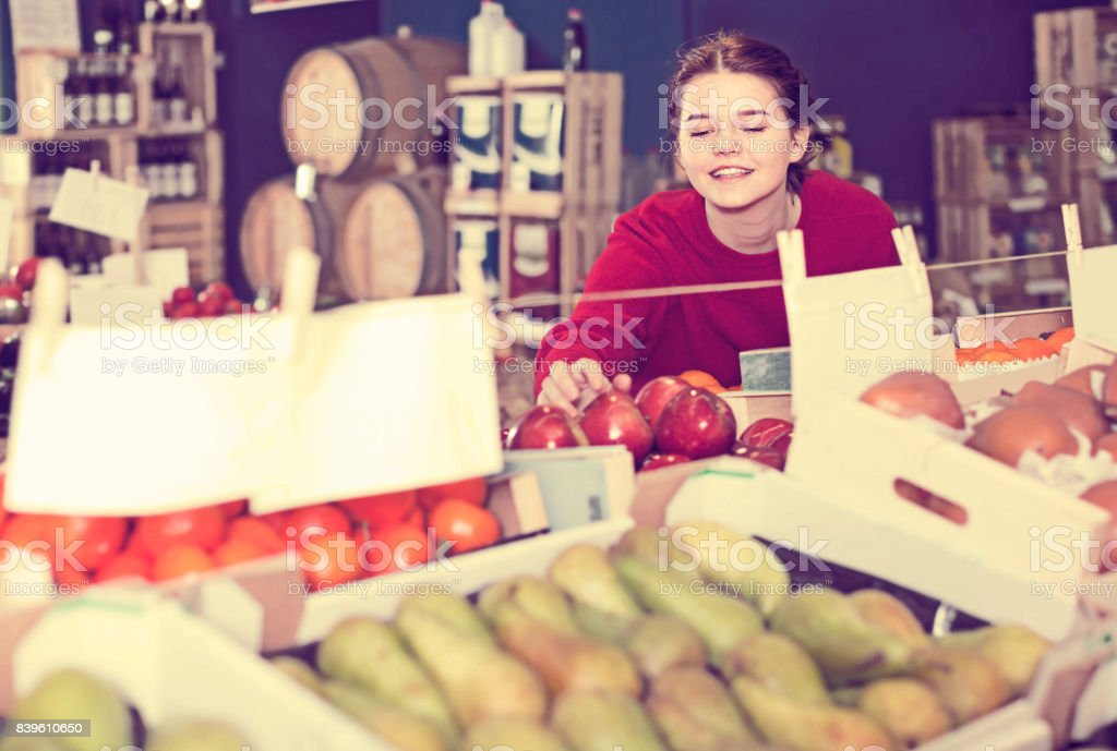 Portrait of young brunette girl buying apple in supermarket stock photo