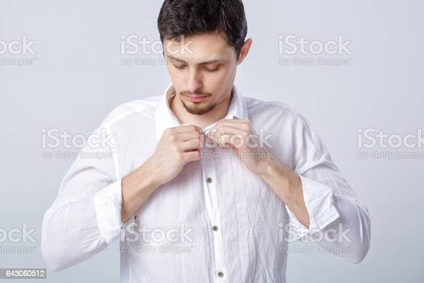 Portrait of young brunette man in white shirt buttoning on grey picture id643060512?b=1&k=6&m=643060512&s=612x612&h=gbp cxeb1klnbapsawdwgoxsqfnmh8e7u06s6ikr7fs=