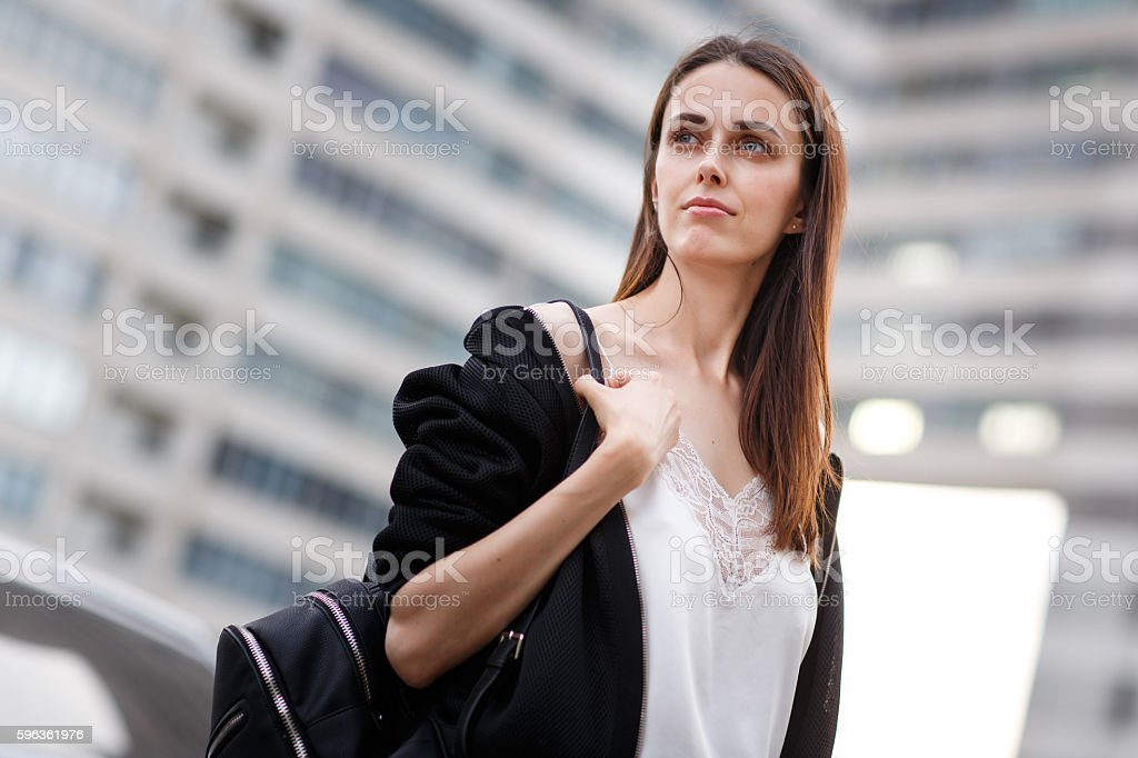 Portrait of young brunette student with backpack on building background royalty-free stock photo