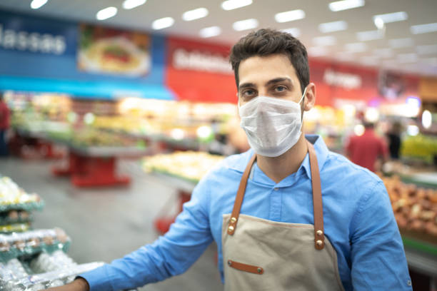 portrait of young business man owner with face mask at supermarket - servizi essenziali foto e immagini stock