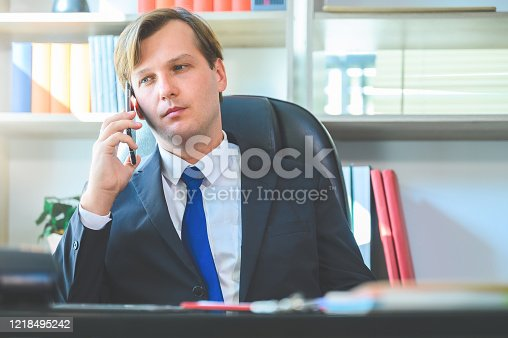 913346608 istock photo Portrait of young business man sitting at his desk in the office and using smart phone 1218495242
