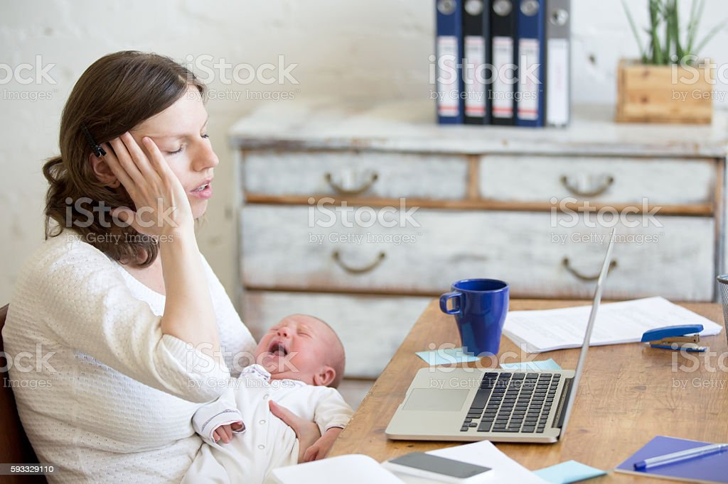 Portrait of young business mom having headache because of crying stock photo