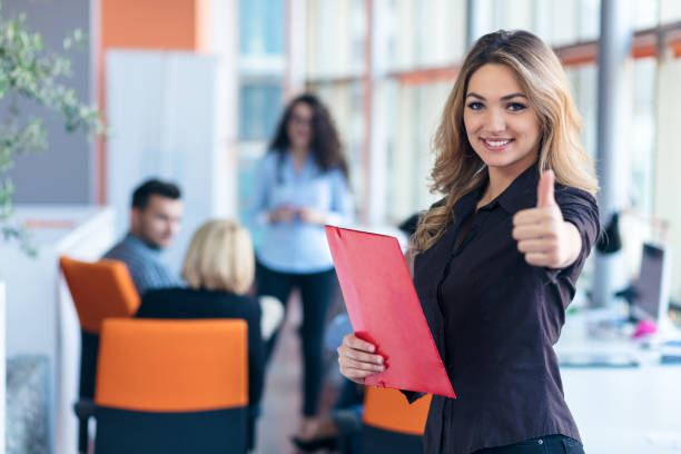 portrait of young business woman at modern startup office interior showing thumbs up stock photo