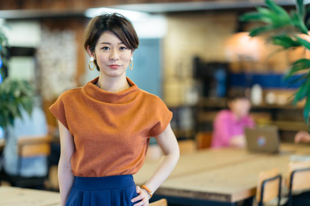 Portrait of young business woman in modenr co-working space A portrait of a young business woman in a modern co-working space. japanese ethnicity stock pictures, royalty-free photos & images