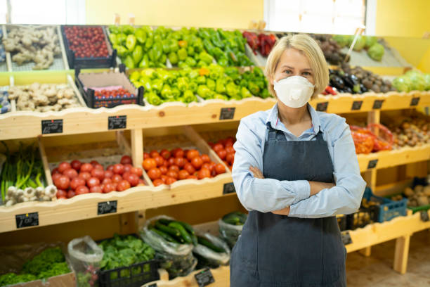 Portrait of young business woman owner of grocery store with face mask