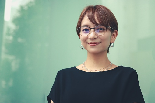 Young asian business woman looking at camera wearing smart casual clothes