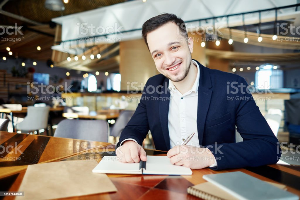 Portrait of young businessman in suit smiling at camera while making notes at cafe table royalty-free stock photo