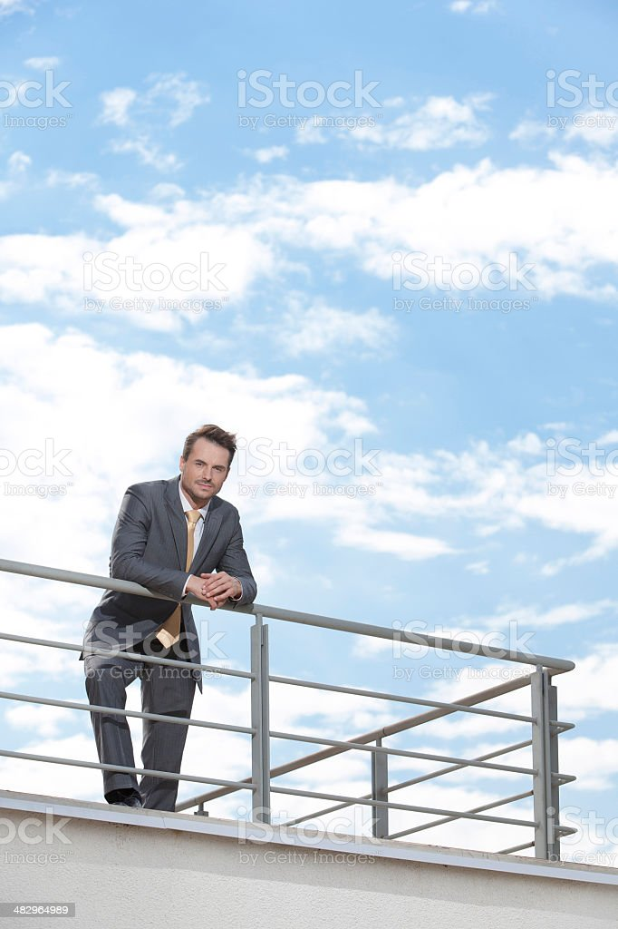 portrait of young businessman leaning on terrace railings stock
