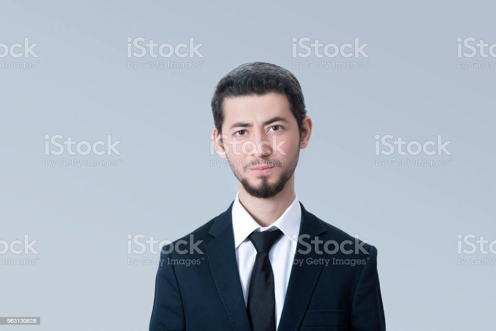Porträtt av ung affärsman tittar på kameran med tomt ansiktsuttryck över grå bakgrund - Royaltyfri 20-29 år Bildbanksbilder