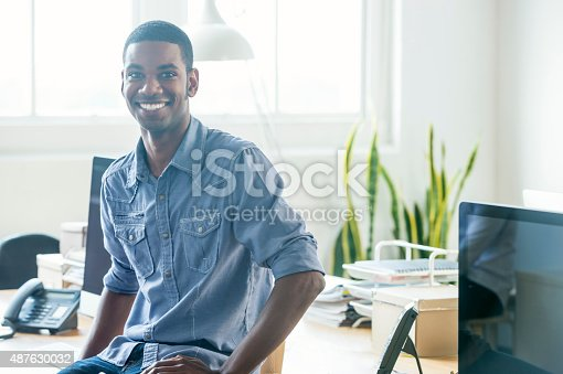 istock Portrait of young businessman sitting on a desk. 487630032