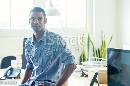 istock Portrait of young businessman sitting on a desk. 487630046