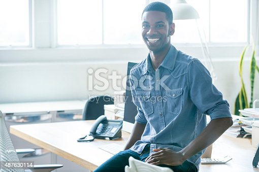 istock Portrait of young businessman sitting on a desk. 487630114