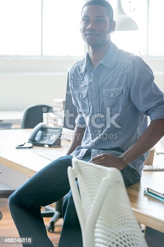 istock Portrait of young businessman sitting on a desk. 488246818