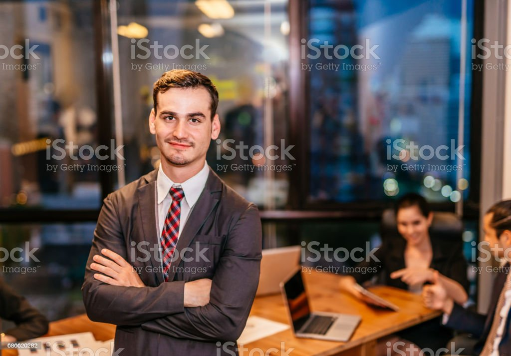 Portrait of young businessman smiling working on modern loft office at night sitting at office with team staff and working late overtime. stock photo