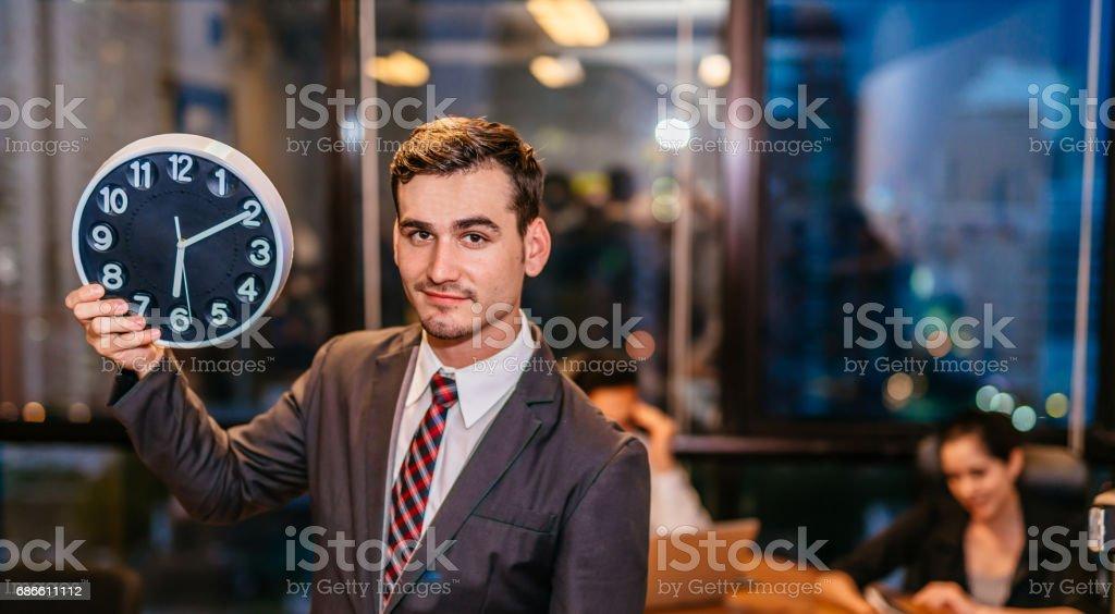 Portrait de jeune homme d'affaires, debout et tenant alarme clock.smiling travail sur bureau loft moderne de nuit assis au bureau avec le personnel de l'équipe et de travailler des heures supplémentaires fin. photo libre de droits