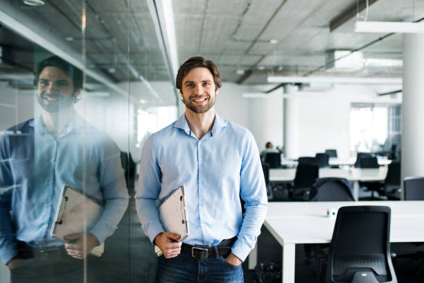 Portrait of young businessman standing in an office, looking at camera. stock photo