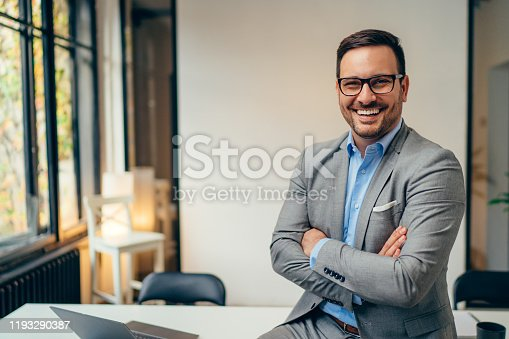 Portrait of young happy businessman wearing grey suit and blue shirt standing in his office and smiling with arms crossed
