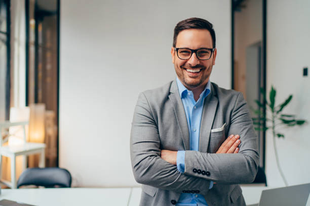 Portrait of young businessman standing in his office with arms crossed stock photo