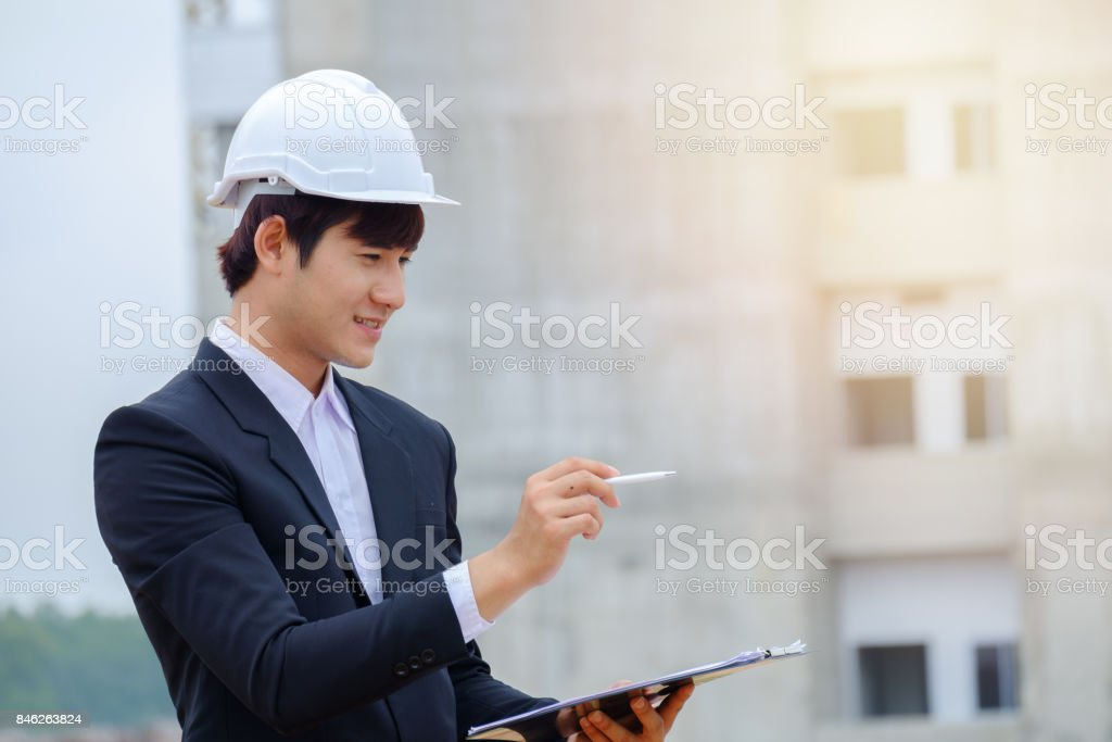 Portrait of young businessman visits building site, Concept Businessman check progress building project  and evaluate profit and Payback time. Copy space stock photo