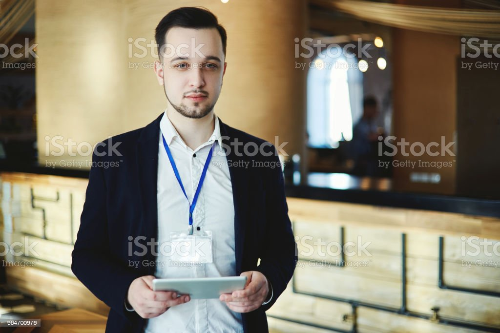 Portrait of young businessman wearing blank badge posing at business event with tablet in his hands royalty-free stock photo