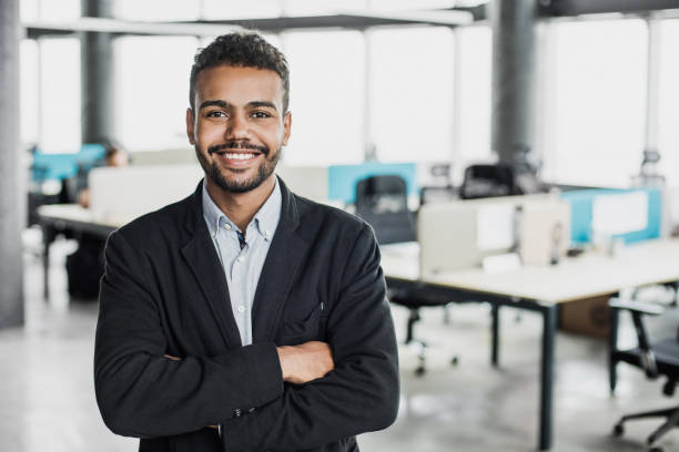 Portrait of young businessman with crossed arms in office stock photo