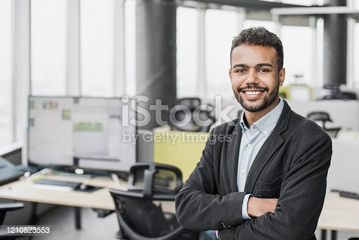 Cheerful handsome young man with crossed hands looking at camera.