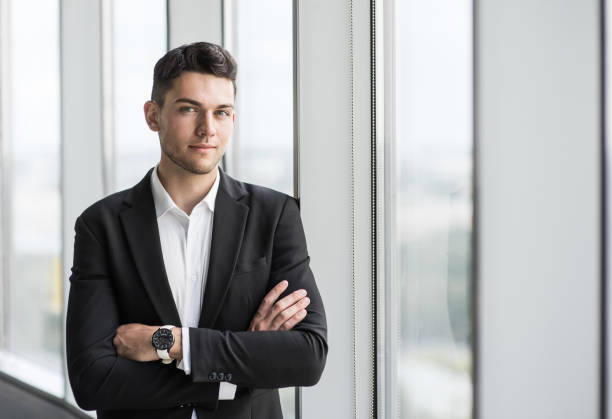 Portrait of young businessman with folded arms in office stock photo