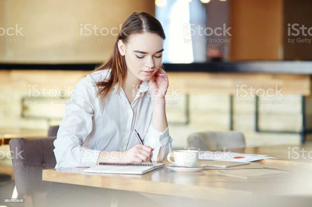 Portrait of young businesswoman in white shirt sitting in cafe and writing in notebook, coffee cup on table royalty-free stock photo