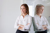 Portrait of young businesswoman leaning against glass wall