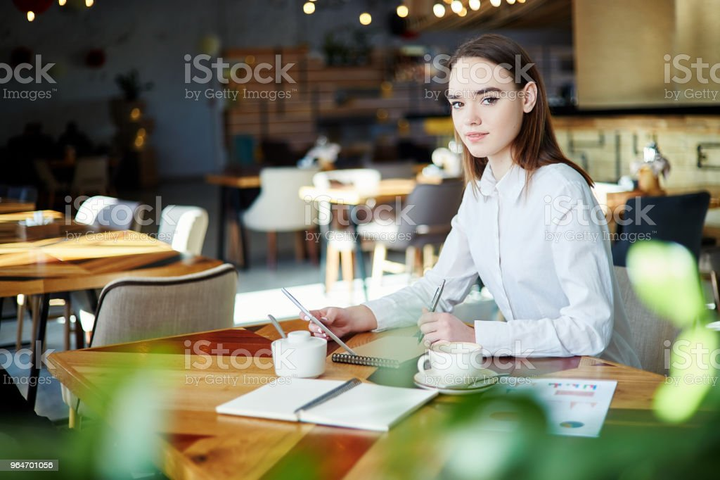 Portrait of young businesswoman looking at camera while working in cafe. Coffee cup, notebooks and documents on her table, pen and tablet computer in her hands royalty-free stock photo