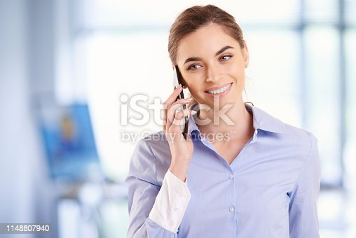 Portrait shot of beautiful young businesswoman wearing shirt while standing in the office and talking with somebody on her mobile phone.