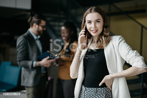 590241864istockphoto Portrait of young businesswoman talking on the phone in busy office 1030328624
