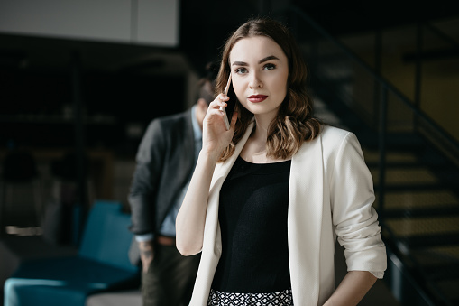 590241864 istock photo Portrait of young businesswoman talking on the phone in busy office 1030329278