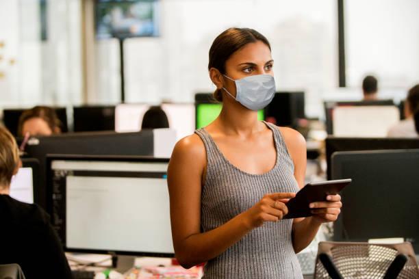 Porträt einer jungen Geschäftsfrau, die eine Gesundheitsmaske trägt. – Foto