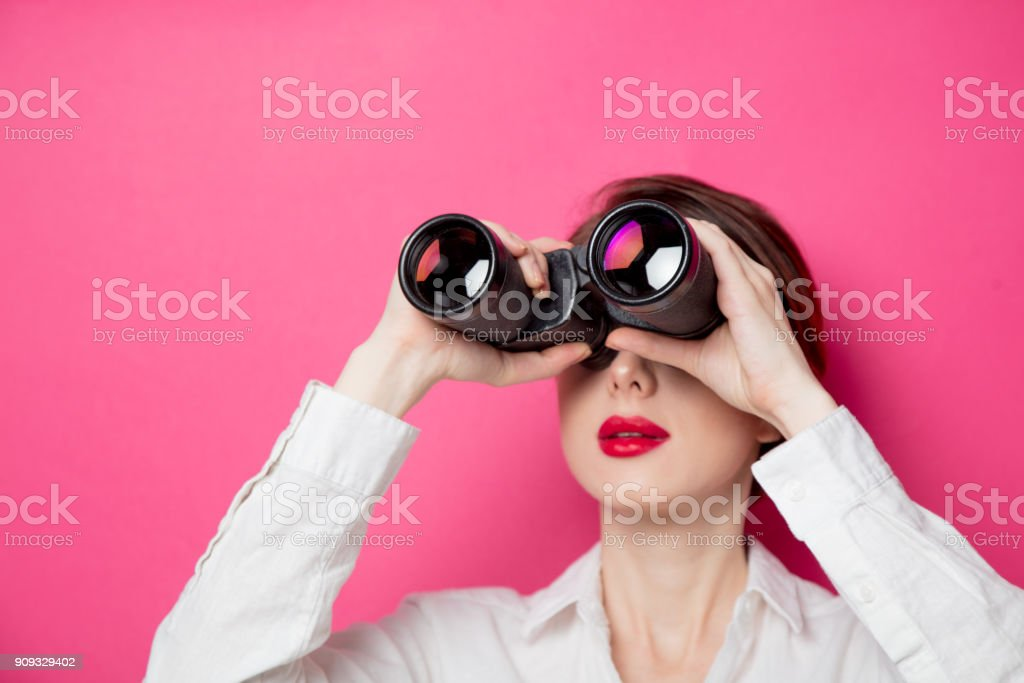 Portrait of young  businesswoman with binoculars stock photo