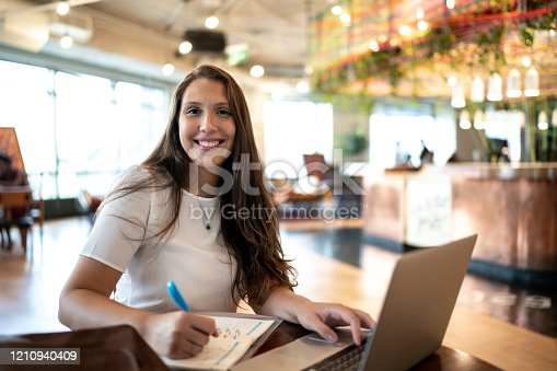 1031394390 istock photo Portrait of young businesswoman working or studying with notepad and laptop at coworking 1210940409