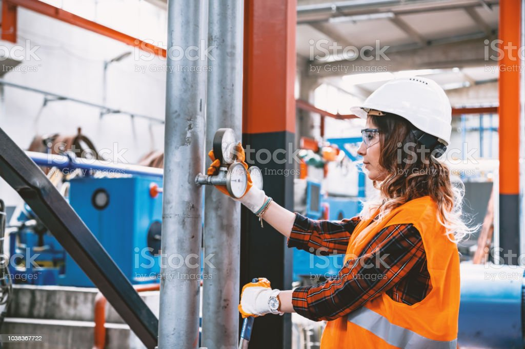 Portrait of young businesswoman working with ball valves in factory stock photo