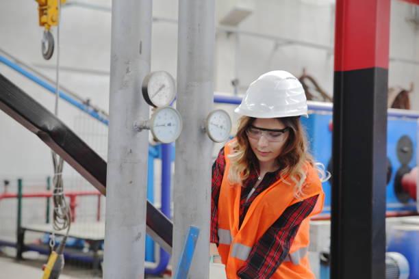 porträtt av ung affärs kvinna som arbetar med kulventiler i fabriken - kvinna ventilationssystem bildbanksfoton och bilder