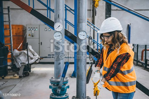 Portrait of a serious technician or engineer woman checking pressure device for industry system, opening or closing valve equipment in industrial site factory or utility.