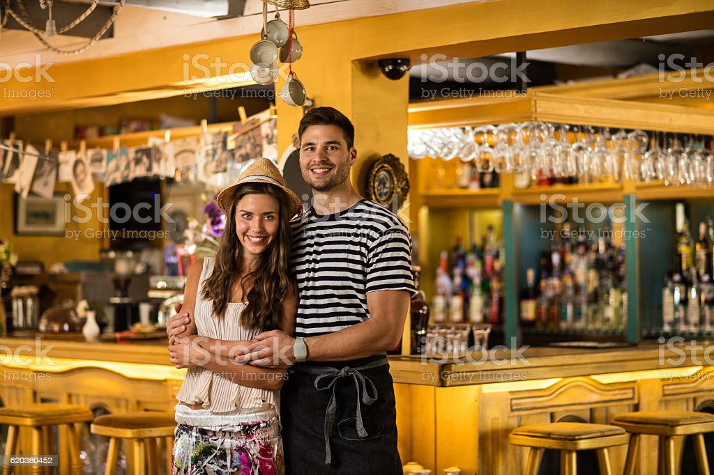 Portrait of young cafe owners standing embraced in their cafe. zbiór zdjęć royalty-free