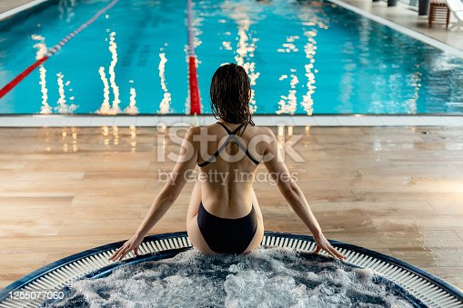 Portrait of young caucasian lady in a spa and hot tub. Modern woman in swimming pool is enjoying and relaxing