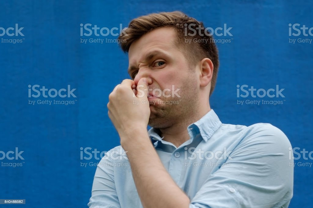 portrait of young caucasian man closing his nose because of terrible smelling stock photo