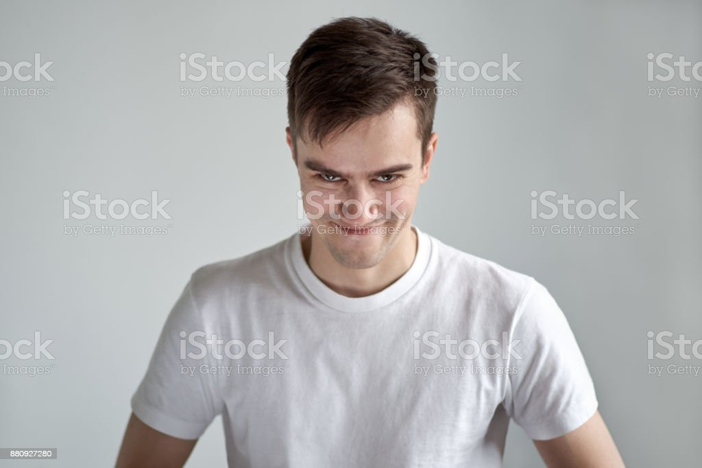portrait of young Caucasian men dressed in white t-shirt with a devilish happy with the look askance came up with a cunning plan and you're satisfied. stock photo