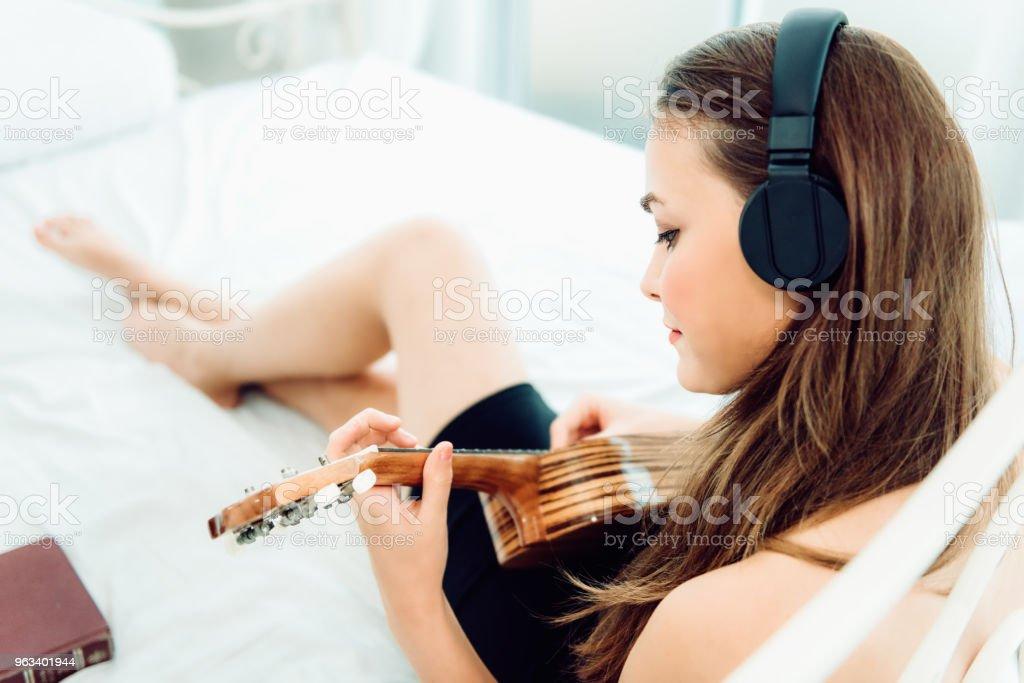 Portret młodej kaukaskiej kobiety siedzącej na łóżku i grającej na gitarze relaksującej się ze słuchawkami, Koncepcja zajęć rekreacyjnych - Zbiór zdjęć royalty-free (Dorosły)