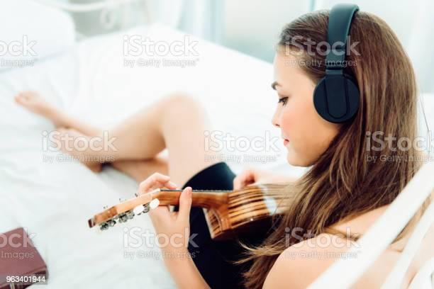 Portret Młodej Kaukaskiej Kobiety Siedzącej Na Łóżku I Grającej Na Gitarze Relaksującej Się Ze Słuchawkami Koncepcja Zajęć Rekreacyjnych - zdjęcia stockowe i więcej obrazów Dorosły
